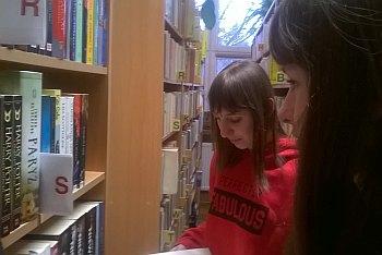 Uczniowie szukają książek wśród regałów w bibliotece
