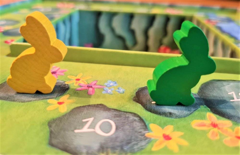 na zielonej planszy przedstawiającej łąkę stoją dwa pionki w kształcie królików