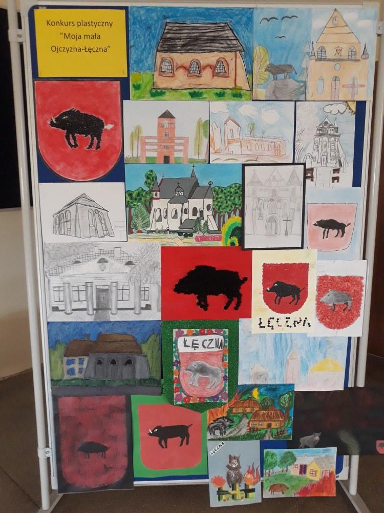 Tablica z pracami uczniów, a na niej prace przedstawiające herb Łęcznej - dzik na czerwonym tle, kościół, synagogę