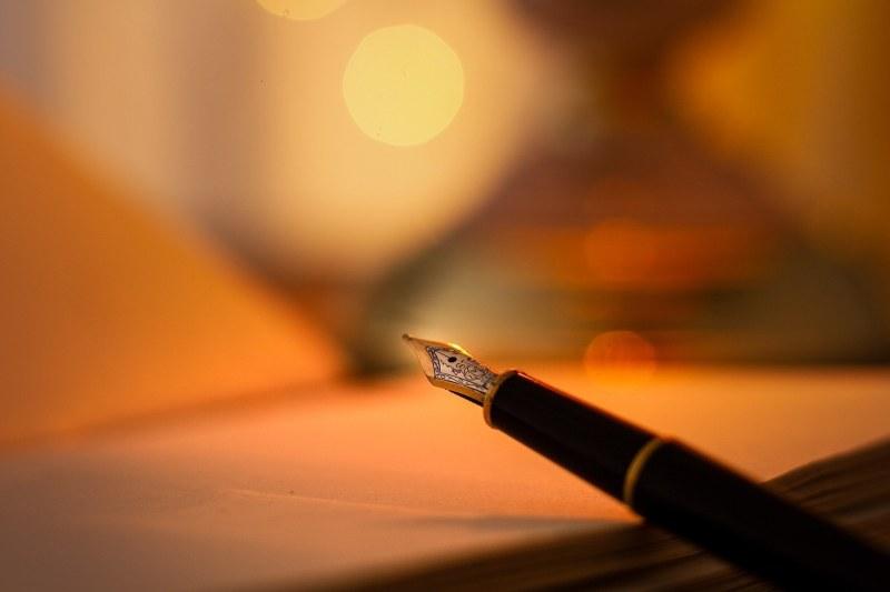 pióro do pisania leży na otwartym zeszycie