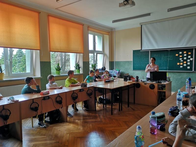 Uczniowie w trakcie debaty. Siedzą wokół okrągłego stołu